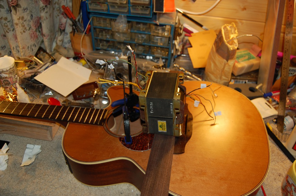 Pickguards cut and being glued on, Partidge 100 Watt Tube amp transformers make great weights!