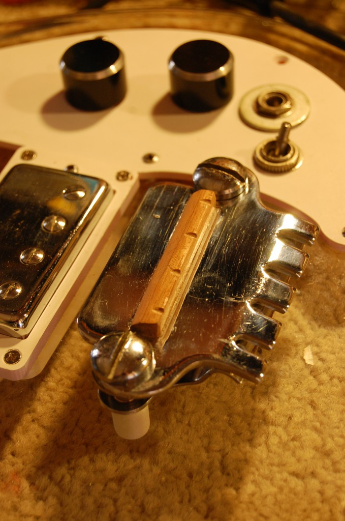 New bridge saddle cut with slits near rear to help improve intonation